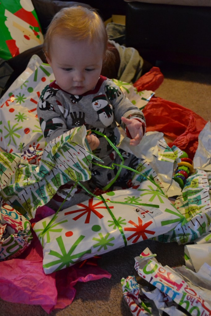 Baby leaning to open presents